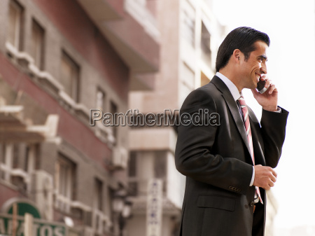 young businessman in street using phone