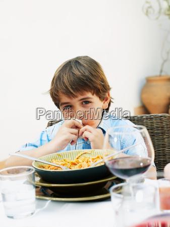boy eating spaghetti at lunch