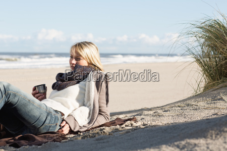 woman drinking from thermos on beach