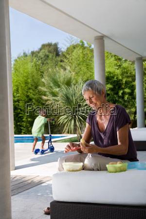woman peeling fruit boy in background