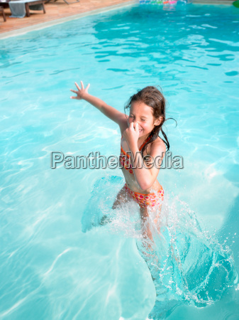 girl jumping in swimming pool