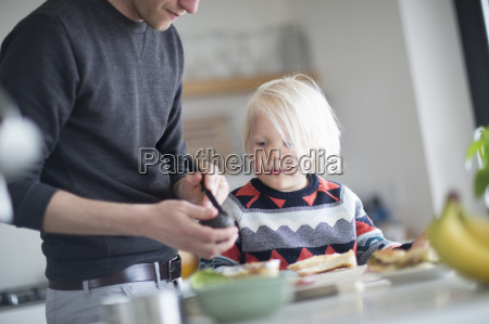 father andf son preparing food in