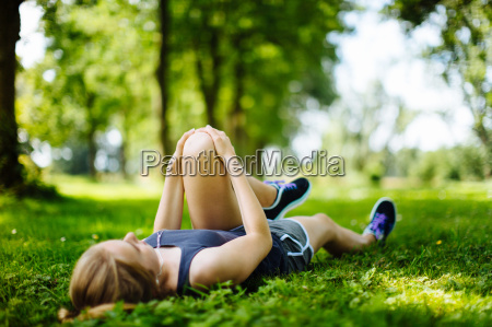 young girl in park lying on