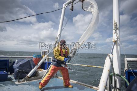 scientist bringing plankton net on board