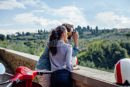 young couple photographing view of hills