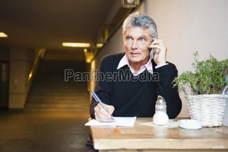 senior businessman making notes whilst chatting