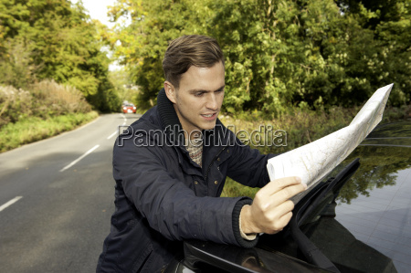 young man reading map on rural