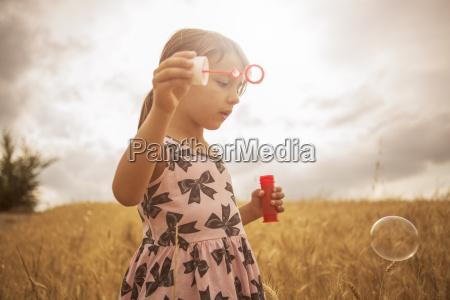 girl blowing bubbles in wheat field