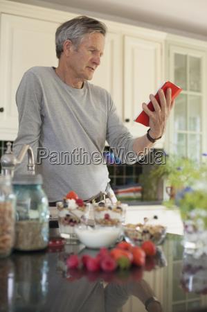 senior man in kitchen looking at