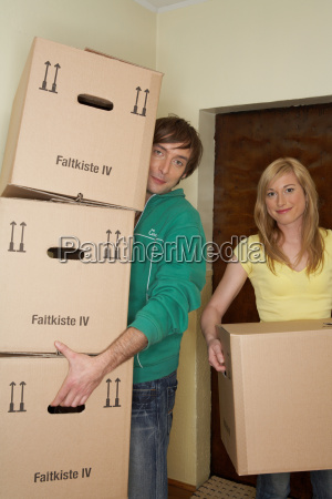 young couple carrying stack of boxes