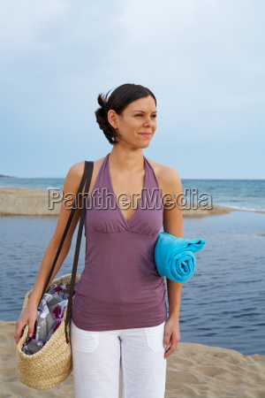young woman with beach bag on