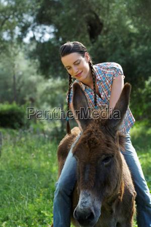 young girl sitting on donkey happy