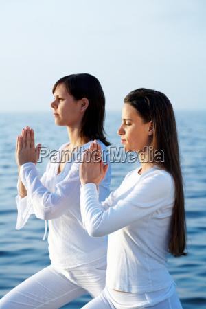 two young women doing yoga by