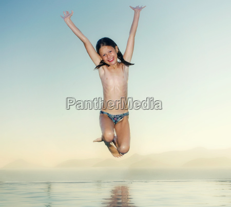 young girl jumping into an infinity