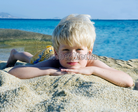 young boy lying in the sand