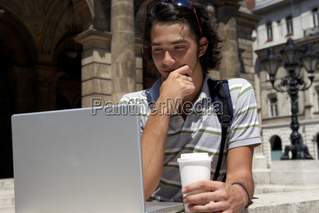 man on laptop by the opera