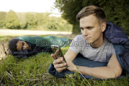 young man lying sleeping bag texting