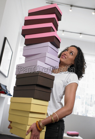 young woman carrying pile of shoe