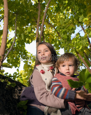 girl holding boy in a tree