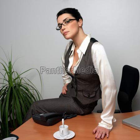 woman sitting on desk portrait