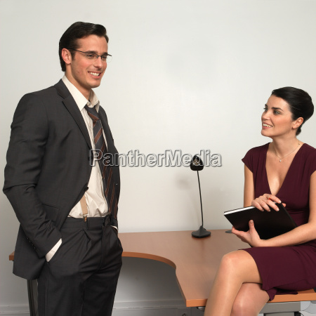 man and woman in office smiling