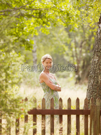 woman standing by wooden fence smiling
