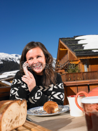 young woman on phone at breakfast