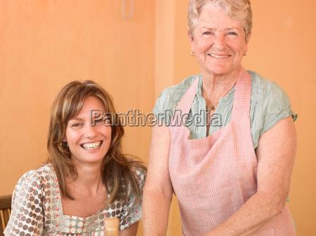 senior woman beside adult daughter