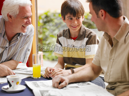 boy sitting in cafe with father