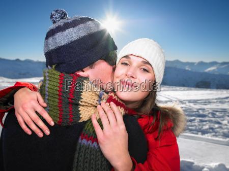 man kissing woman on mountain top