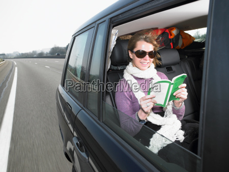young woman reading in car