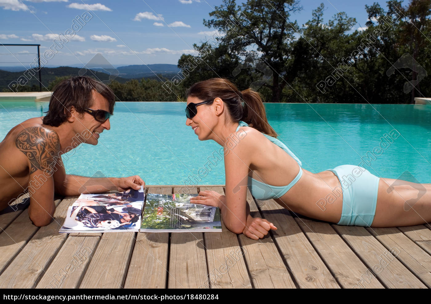 couple, sunbathing, by, a, swimming, pool - 18480284