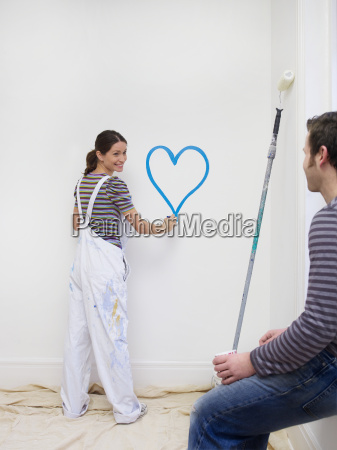 young woman painting heart on wall