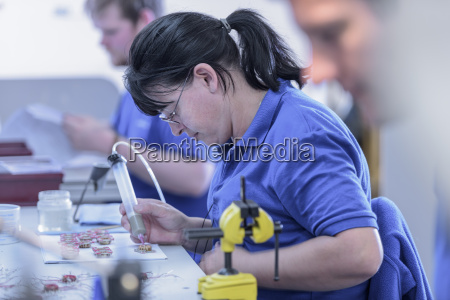 female worker assembling electromagnets on production