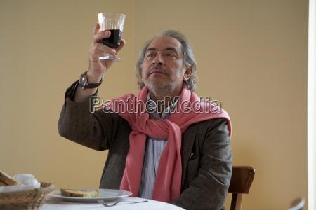 senior adult man looking at wine