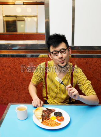 young man eating fried meal