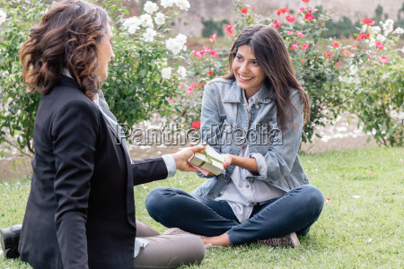 lesbian couple sitting on grass giving