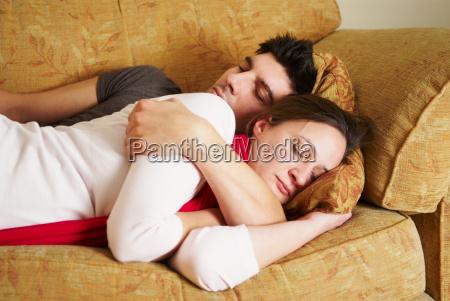 embracing couple lying on sofa