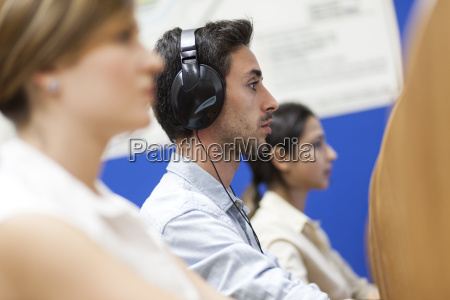 young man sitting wearing headphones
