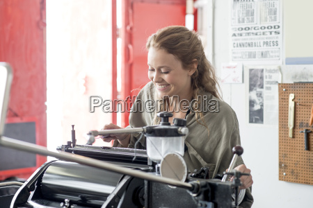 female letterpress printer preparing printing machine