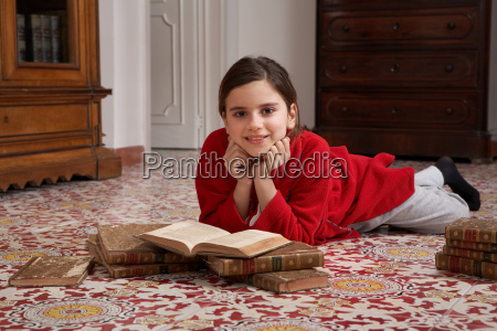 girl lying on floor reading books