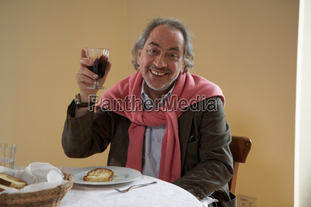 senior adult man holding up wine