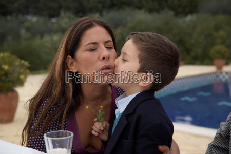 mother kissing son at the table