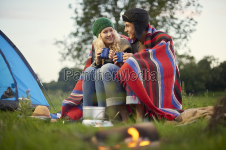 young camping couple sitting by campfire
