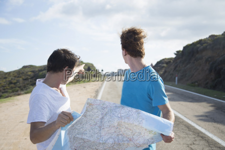 young men on road holding map