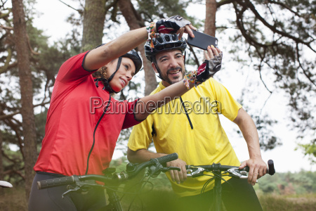 happy mountain biking couple taking smartphone