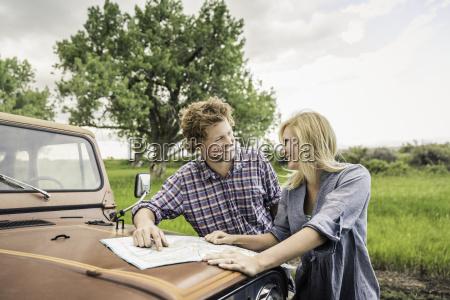 teenage girl and boyfriend reading map