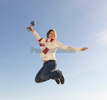 woman jumping holding trophy