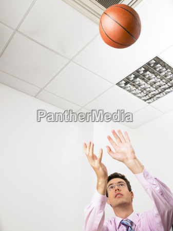 businessman in an office throwing a
