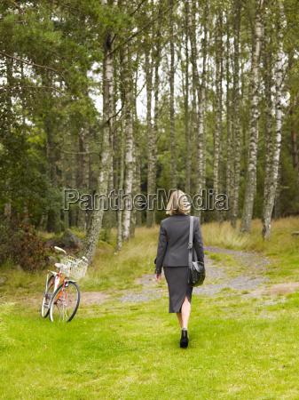 businesswoman walking in woods